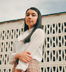 young woman in a shirt standing in front of a concrete wall gazing down