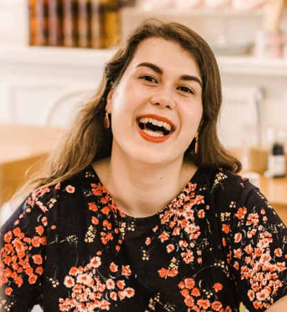 smiling woman wearing red lipstick and colourful shirt