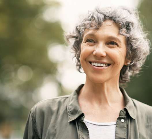 woman smiling with grey hair wearing a shirt